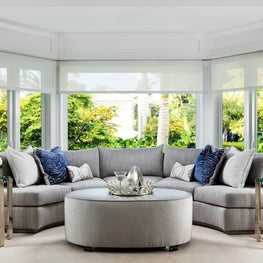 Curved light grey upholstery sofa in this contemporary light infused family room.