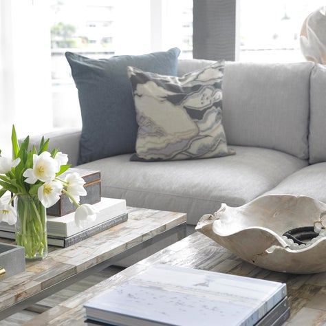 Monochromatic gray sofa, pillows & accessories. Bleached wood & metal tables.