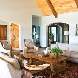 Great room with wood vaulted ceilings and exposed beams in cream and grey.