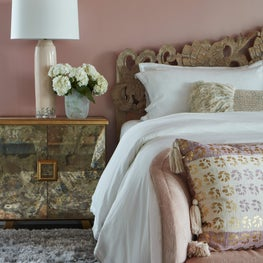 Elegant layering in this dusty pink, boho chic master bedroom