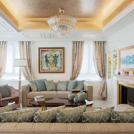 A sophisticated and elegant living area, with gold-leaf gilded living room ceiling, hi end fabrics, fine cabinetry and a fireplace.