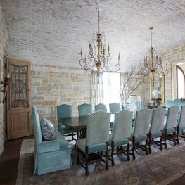 Brick ceiling dining room with antique French chandelier and reclaimed doors
