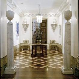 Classical foyer with geometric wood floors, molding
