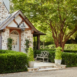 Rear entry garden with Holly hedges and Crape Myrtle by Howard Design Studio.