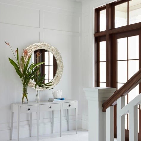White minimal entry with contrasting dark wood trim.