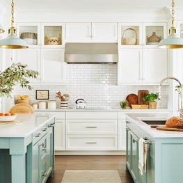 Mint green kitchen with hanging pendants marble counter tops and painted island with rattan counter stools