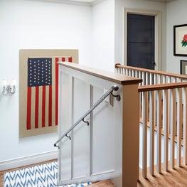 48 star Flag hangs over blue & white ikat stair runner, gray trim and navy doors