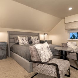 Open Plan Fusion -  Cozy bed, nightstands, lounge chairs, bedding and custom pillows in greys with custom window trim
