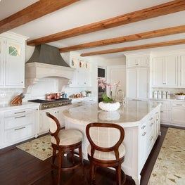 White Kitchen with Stone Hood and Natural Beams