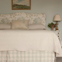 Bedroom in coastal home with a custom headboard and white wash bedside tables
