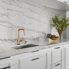 Custom white kitchen with full height quartzite backsplash.