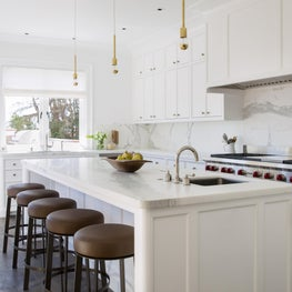 White kitchen with leather bar stools, brass pendants, and woven window shades.