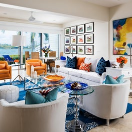 This neutral living room has pops of orange and blues like the ocean.