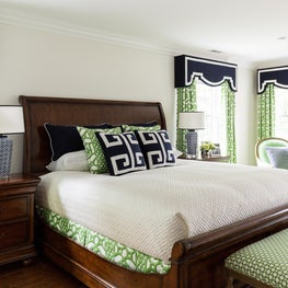 This neutral bedroom is accented with bold navy and green patterned textiles.
