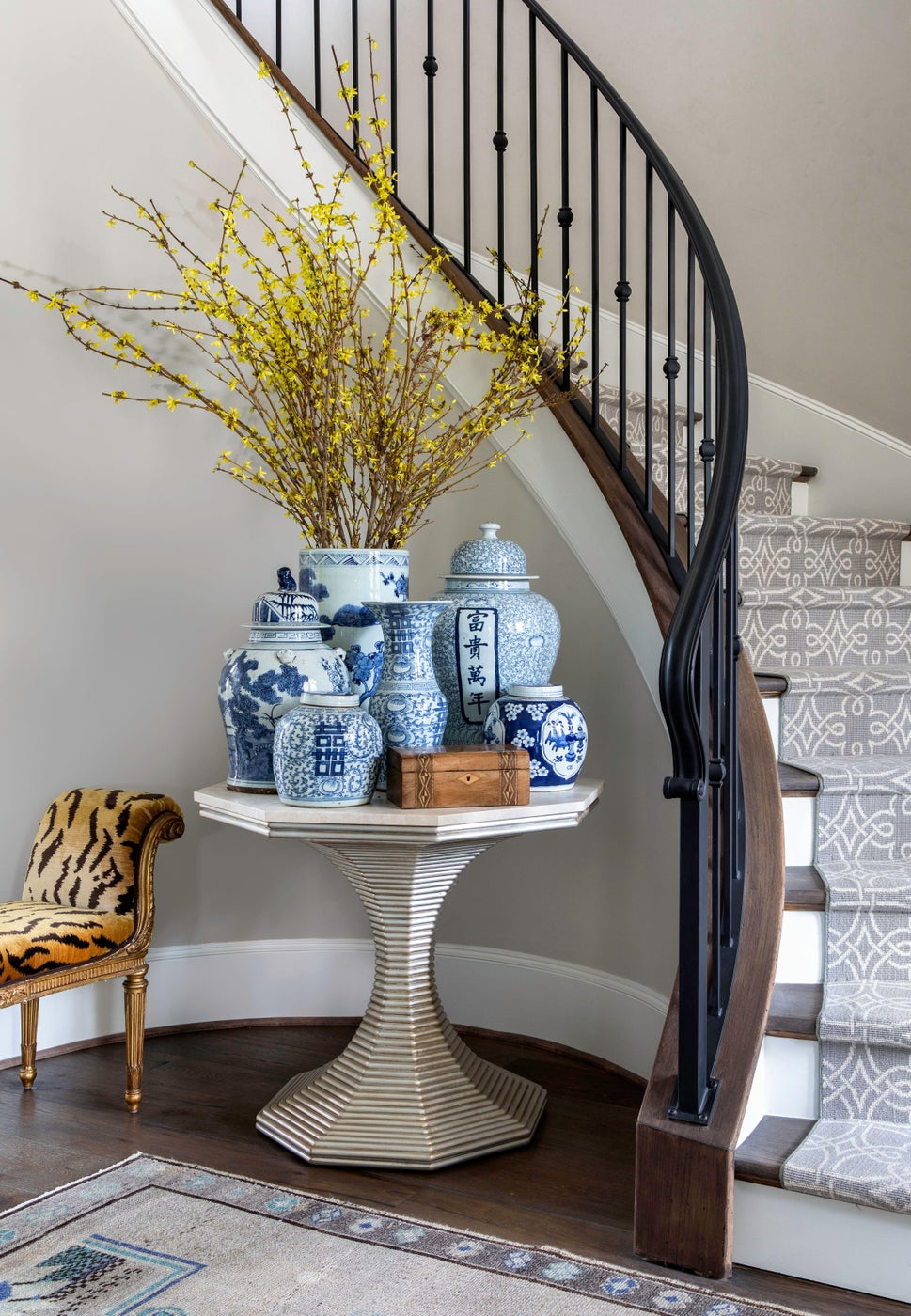 Formal entry hall & stairway with patterned runner & blue-and-white porcelain