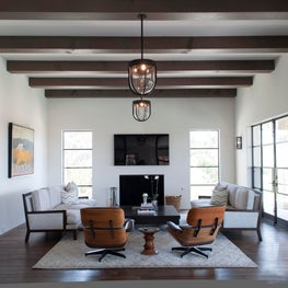 Plenty of room to watch a Padres game in this family room:  two Eames chairs, two comfy sofas, all near a cozy fireplace.