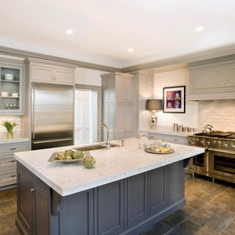 Classic taupe inset kitchen with gray island, wood hood, and marble backsplash