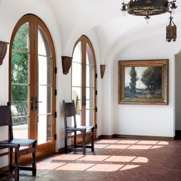 The interior of the loggia features a hex tile floor and groin-vaulted ceiling