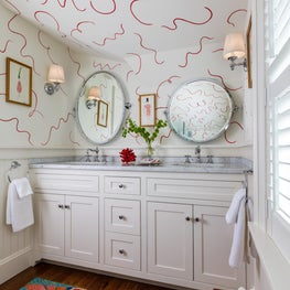 Whimsical powder room with bright patterned rug and white painted walls with red swirls.