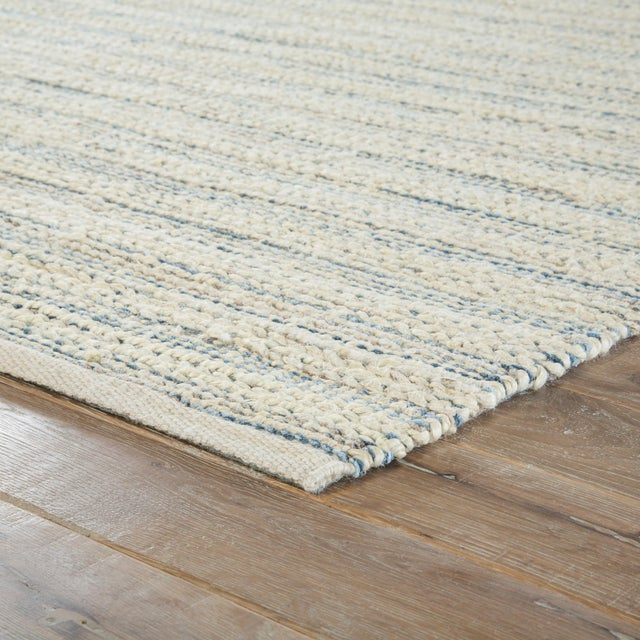A natural area rug with a contemporary touch, this cotton-backed layer pops with a bleached white tone and hints of blue...