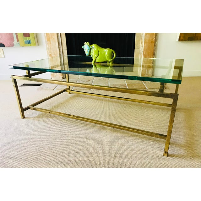 This brass and glass floating coffee table has some serious understated mid century chic. Half inch thick glass on metal...