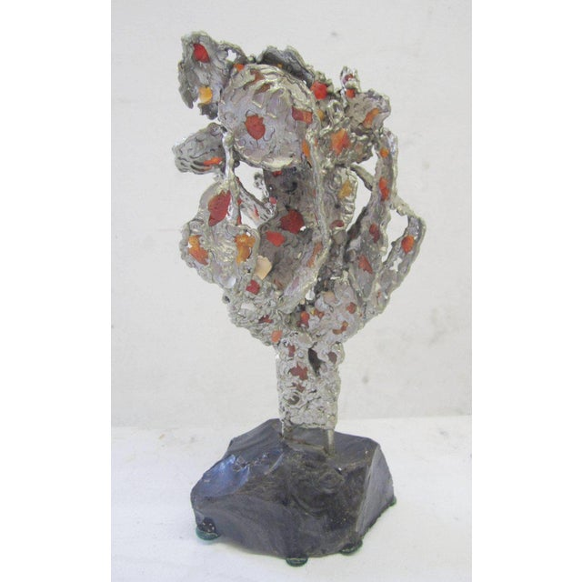 Abstract lead sculpture with agate inserts on an obsidian base.