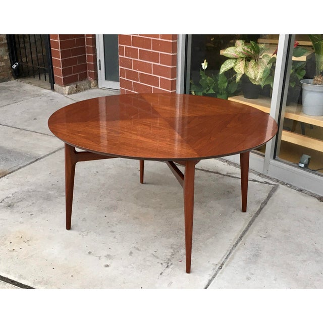 One-of-a-kind cocktail table with amazing stretcher joined carved mahogany legs that support a table top of book matched...