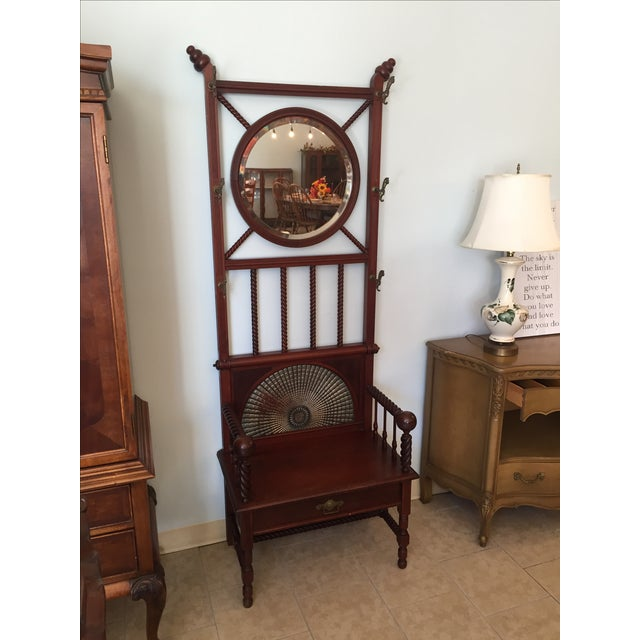Antique hallway entry piece. Very beautiful Mahogany colored halltree. Has a seat with arm rests and drawer under the...