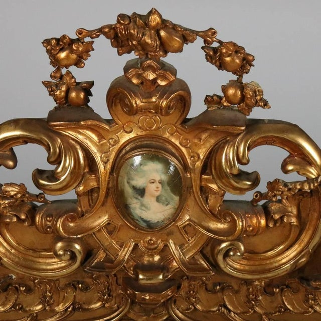 Monumental antique French Louis XIV over mantel mirror features pierced scroll and foliate giltwood surround with central...