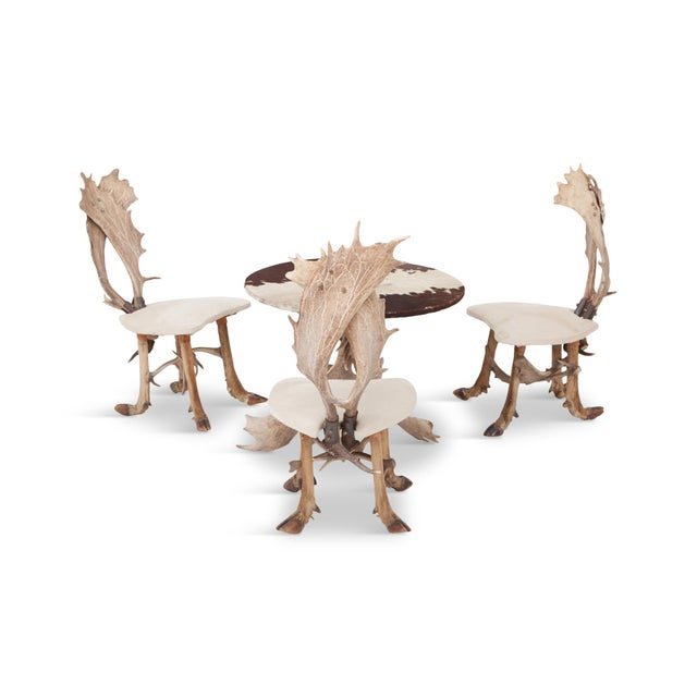 Hunting chairs and matching center table. The back of the chairs are made of two deer antlers while the legs are...