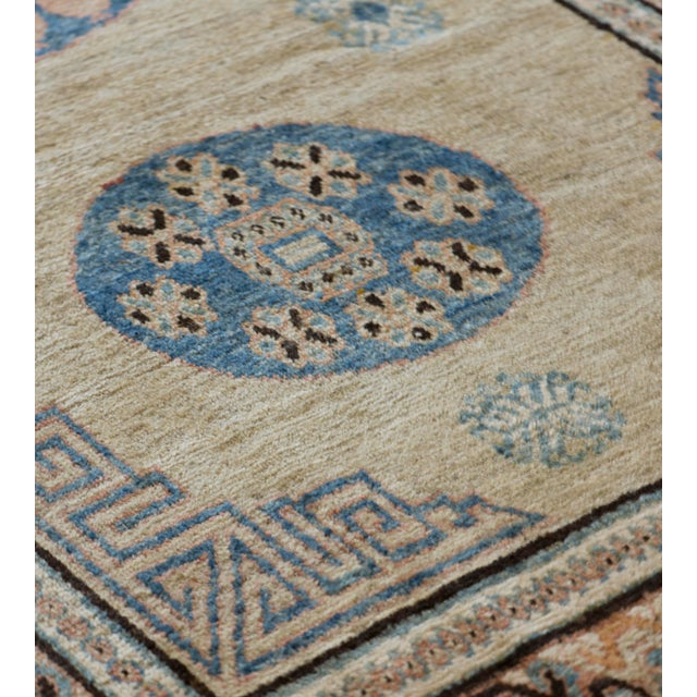 This antique Khotan rug has a shaded sandy-yellow field with six ivory and light blue hooked floral motifs around a column...