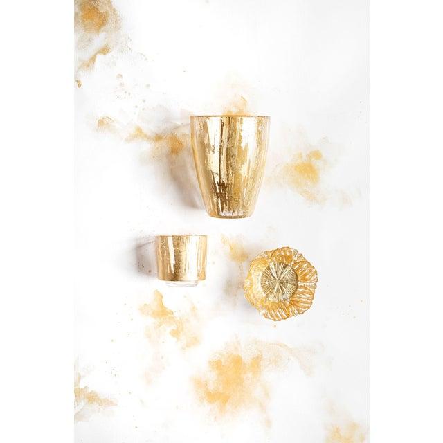 The Rufolo Gold Brushstroke Votive The Rufolo Glass Gold Brushstroke Votive brings luster to your table. The glass piece...