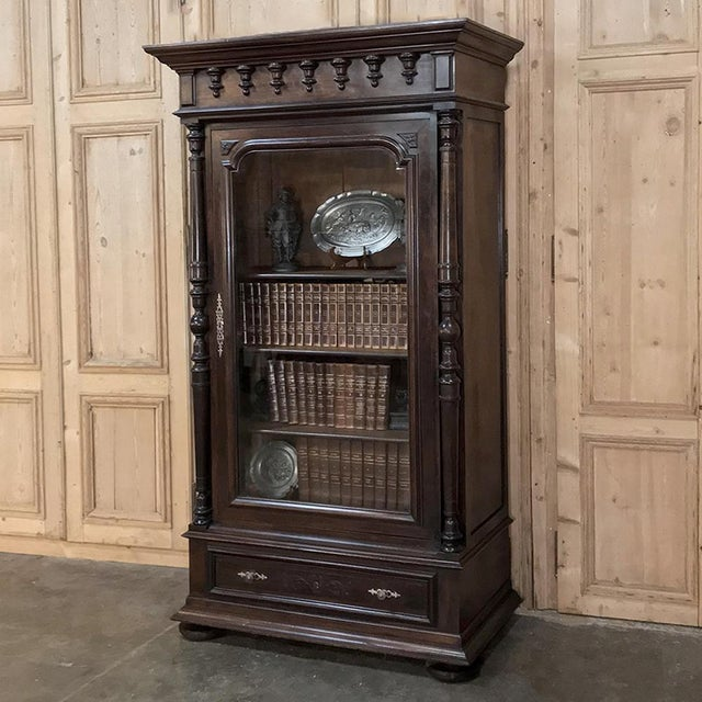 19th Century Neoclassical French Walnut Display Armoire features a stately presence, and a revival of ancient Greek...