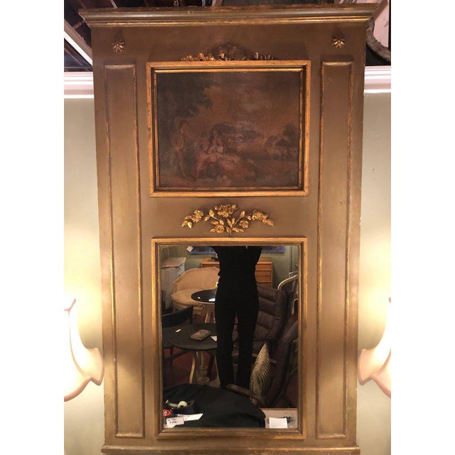19th century trumeau mirror. French paint decorated frame with a fine carved crest. The top having an oil painting of...