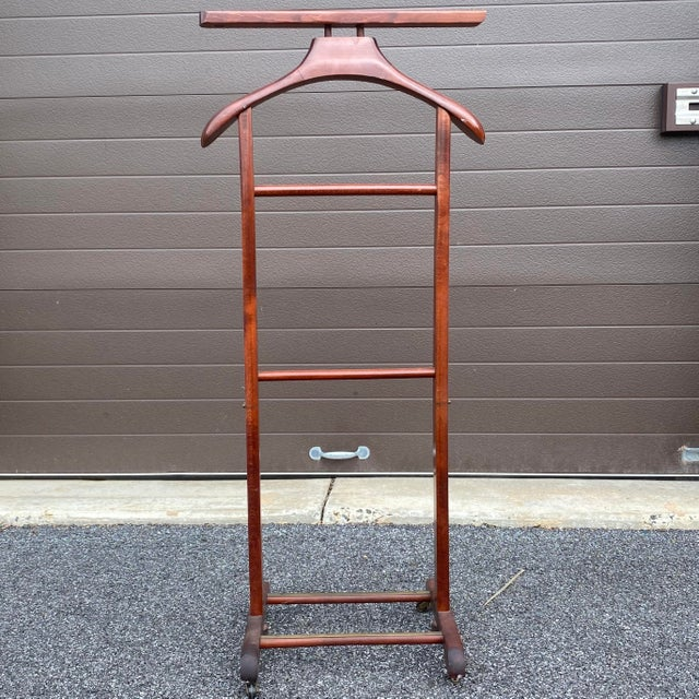 Vintage Italian valet in lovely cherry finish with brass hardware. The wood appears to be maple or a similar hardwood....