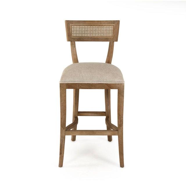 Curved cane back bar stool upholstered in natural cream linen on limed grey oak frame.