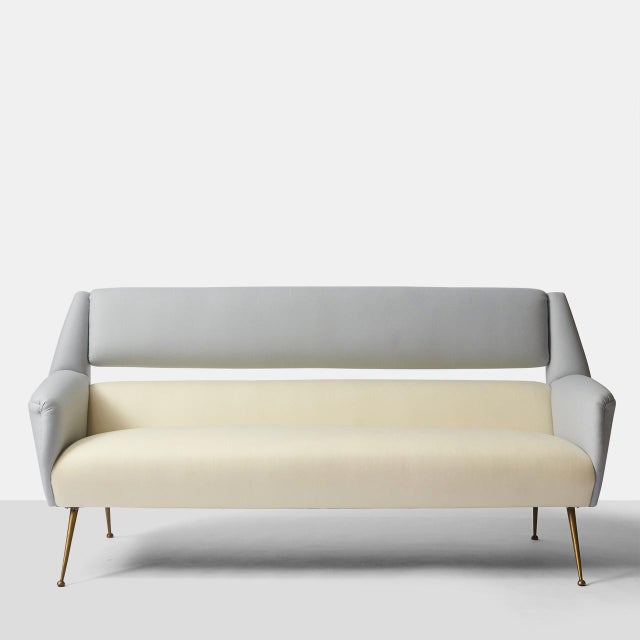 A sofa with tapered brass legs and a two-tone wool upholstery in ivory and grey. Freshly reupholstered in wool from...