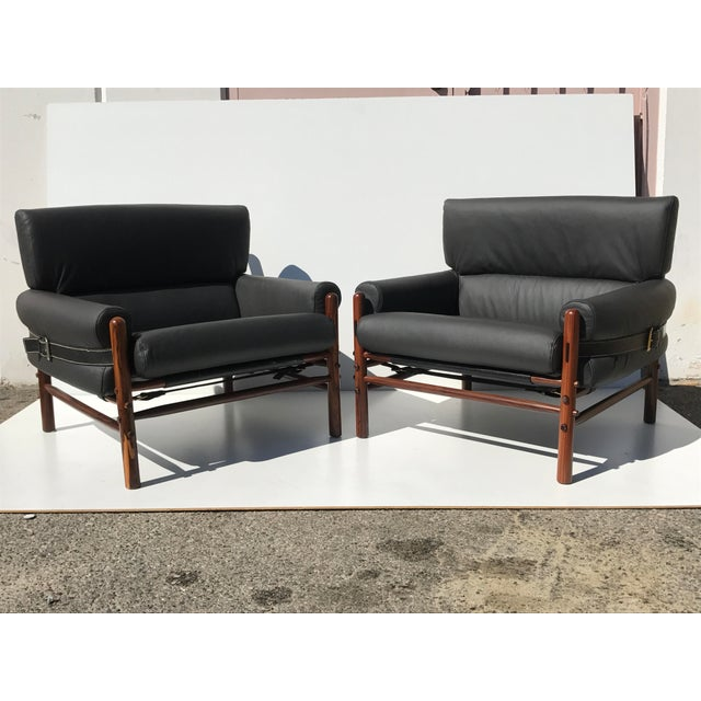 Pair of Arne Norell Kontiki model safari lounge chairs. Rosewood frames have been refinished and some straps been...