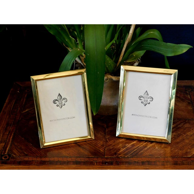 This pair of brass frames feature glass inserts. Perfect to style any shelf or table. Will fit 5X7 pictures.