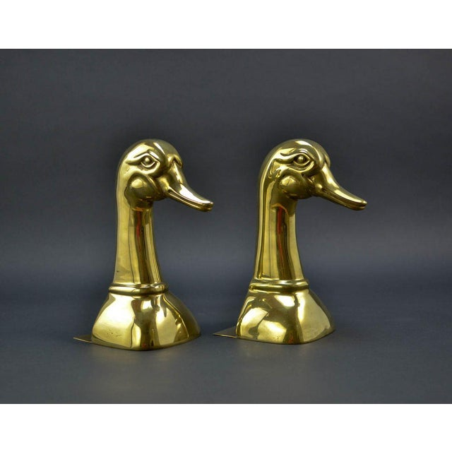 Beautiful mid-century pair of large brass duck's head book supports, produced by Sarreid, USA 1970s The labeled set is in...