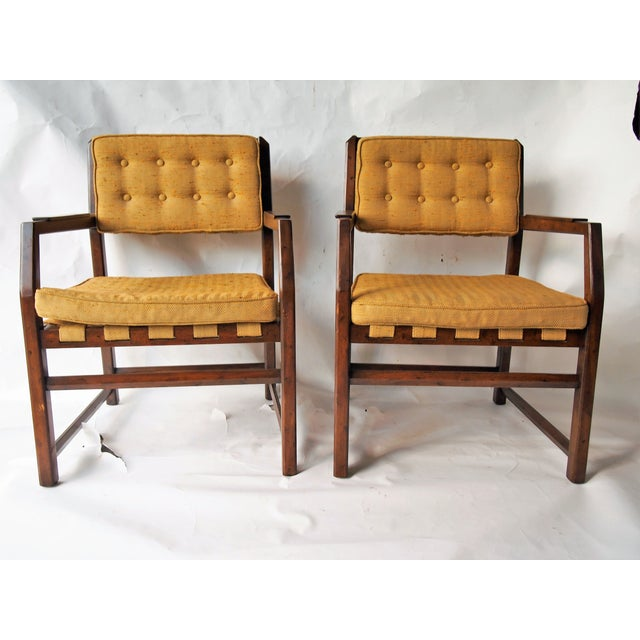 A pair of Mid-Century Modern armchairs with walnut frames and tufted backs with cross webbing support. Original...