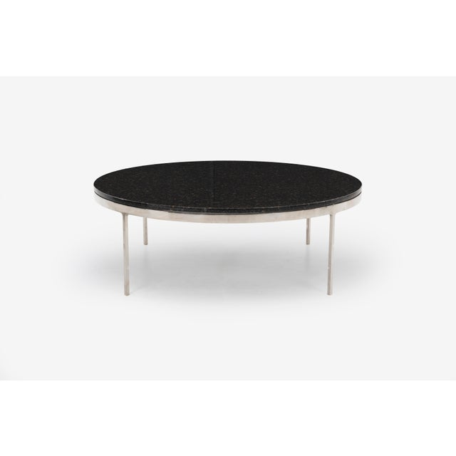 Circular coffee table with granite top and chrome plated base.