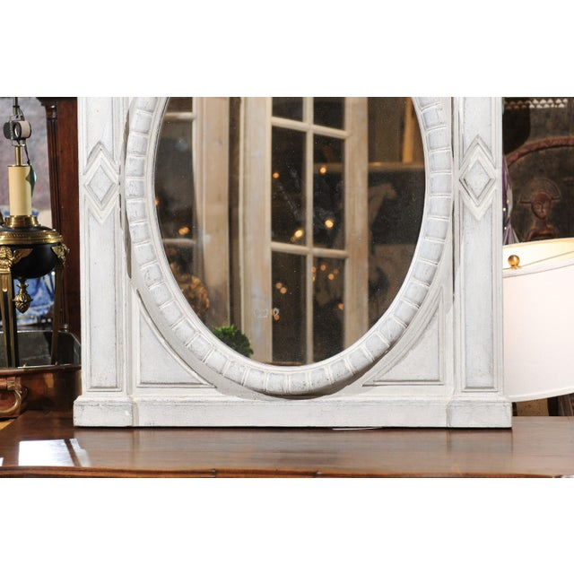 A Renaissance style Belgian painted wood mirror from the mid-19th century, with broken arch pediment and oval mirror...