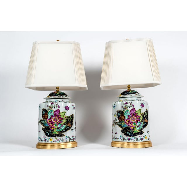 Late 20th century French porcelain pair table lamps with giltwood base with floral design details. Each lamp is in...
