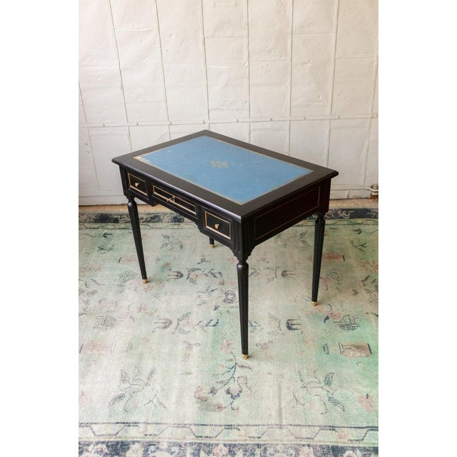 Early 20th century writing desk with three drawers. Ebonized Mahogany with original (distressed) leather. Sold as is.