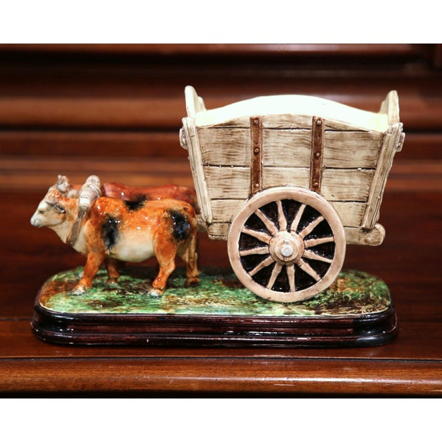 This colorful, antique Majolica sculpture depicts a Classic farm scene with cows pulling a cart. Created in France circa...