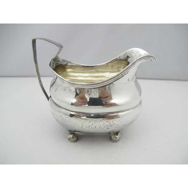 George III squared cream pitcher, bow belly form with thread edging all resting upon bun feet. No city mark, maker...