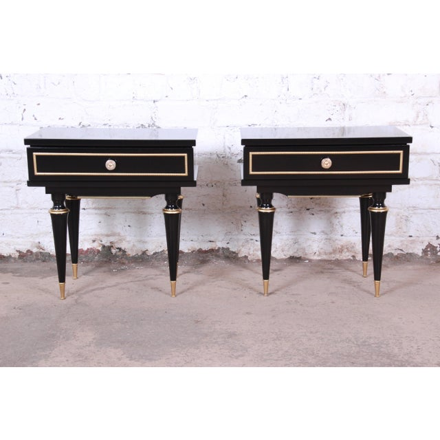An outstanding pair of French mid-century modern nightstands or end tables. The nightstands feature a high gloss ebonized...