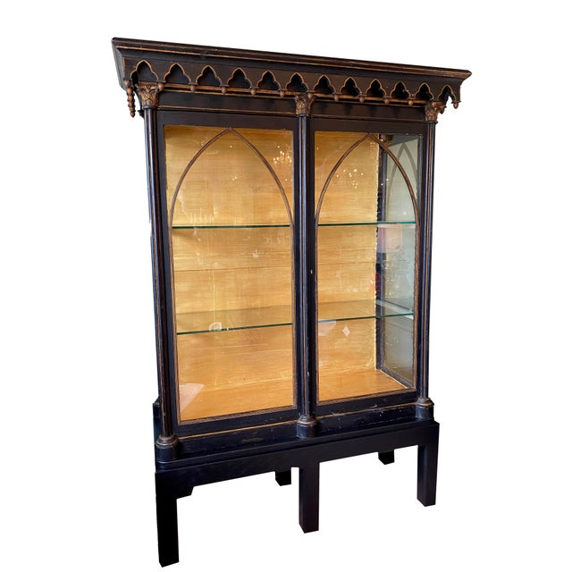 Antique Gothic style cabinet with scalloped top, glass doors with arch accents and glass shelves, on a custom wood base....