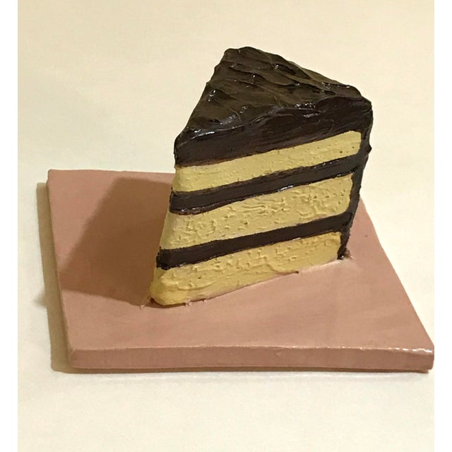A little slice of chocolate cake on a tile. I build the cake slice from stoneware clay and sculpt the frosting and...